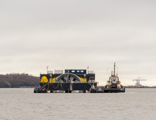 A Giant Tidal Turbine Being Delivered For Installation On The Ocean Floor. Turbine Is Held By A Delivery Ship That Is Being Moved By A Tugboat. ID Has Been Removed From The Boats. Sky Is Overcast.
