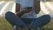 Woman sitting in yoga position on grass and listening to music on smart phone