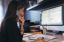 Woman Using Cellphone At Desktop