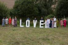 Wedding Guests Posing Behind Love Word