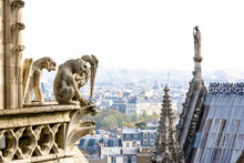 Three Stone Statues Of Chimeras Overlooking The Rooftop Of Notre-Dame Cathedral And The Historic Center Of Paris From The Towers Gallery With The City Vanishing In The Mist In The Distance.