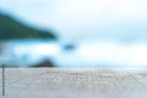 Montage in der Fensternische Licht blau Selective focus of old wood table with beautiful beach background for display your product.