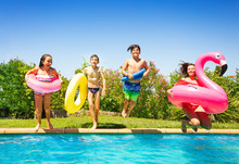 Happy Teens With Swim Tools Jumping Into The Pool