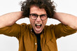 Portrait of unhappy man with curly hair opens mouth widely, screams loud with hands on head, wears round glasses posing on against white wall. Nervous student male shouting. People, negative emotion