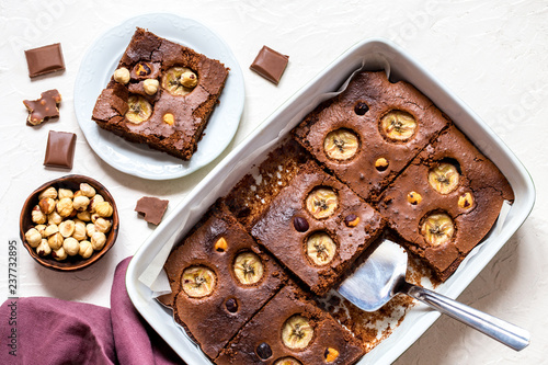 Fototapeta brownie with banana and hazelnut on white background in the form of pieces obraz