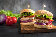 Two Homemade Turkey Burgers With Salad, Tomatoes, Pickles And Red Onion On Wooden Cutting Board