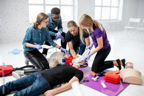 Group of young people during the first aid training with instructor showing how Fototapet