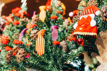 Traditional Spanish Flag Colors On Christmas Pine Tree In Market Among Decorations In Winter With Gnome