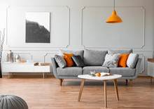 Orange Lamp Above Wooden Table In Front Of Grey Sofa In Living Room Interior With Poster. Real Photo