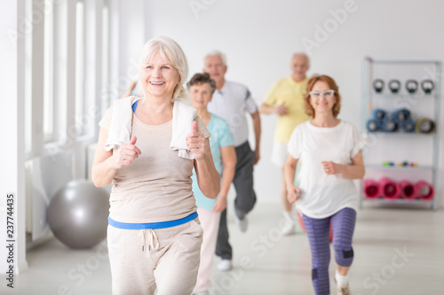 Happy active senior woman with towel exercising during physical classes for elde Canvas Print
