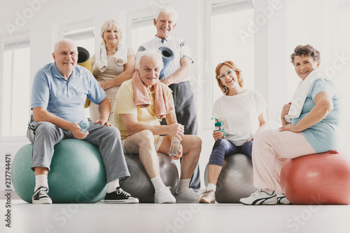 Fotografija  Low angle on smiling active elderly people on balls after physical classes in sp