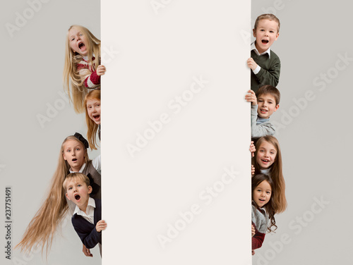00ecc69b745 Banner with a surprised children peeking at the edge with copyspace. The  portrait of cute little kids boy and girls ...