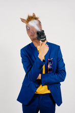 Unrecognizable Man Disguised With A Horse Head And Dressed With A Blue Suit Posing In A Studio Set