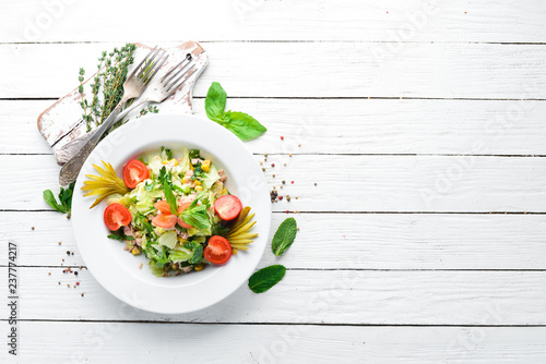Tuna salad and fresh vegetables on a white wooden background. Free space for your text. Top view.