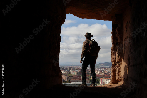 Fotografie, Obraz EXPLORER WITH AUSTRALIAN HAT AND BACKPACK OBSERVING THE CITY FROM A HIGH CAVE