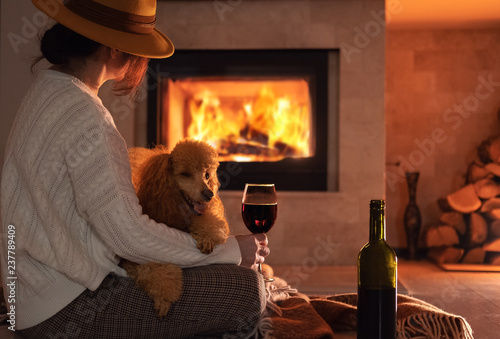Woman traveler with her dog sits at the floor and drinking wine on the fireplace background .