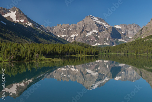 Poster Bergen Reflections of the rugged mountains towering above the forested shores can be seen in Swiftcurrent Lake on a beautiful summer day in Glacier National Park