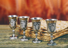 Passover Background Four Glasses Wine And Matzoh Jewish Holiday Bread Over Wooden Board.