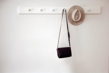 Stylish Hat And Small Black Purse Hanging On White Pegs On Wall In Cozy Room