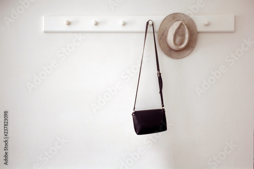 Obraz na plátně  Stylish hat and small black purse hanging on white pegs on wall in cozy room
