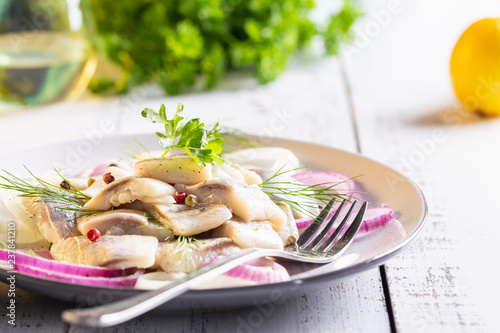 Herring pickle with onion, oil, pepper and dill on plate.