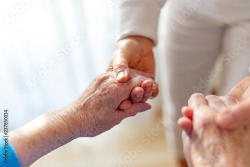 Fotografie, Tablou  alte Frau wird von einer Pflegerin an den Händen gehalten