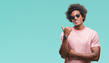 Afro American Man Wearing Sunglasses Over Isolated Background Smiling With Happy Face Looking And Pointing To The Side With Thumb Up.