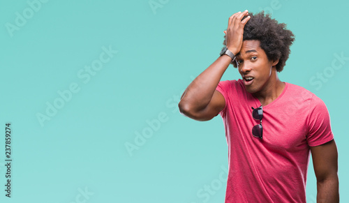 Fotografie, Obraz  Afro american man over isolated background surprised with hand on head for mistake, remember error