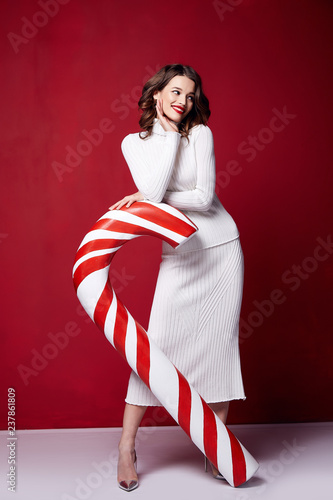 Sexy pretty lady fashion model beautiful woman wear style skinny knitted white color dress celebration happy holidays merry Christmas Eve new year party hold candy cane caramel brunette makeup. Wall mural