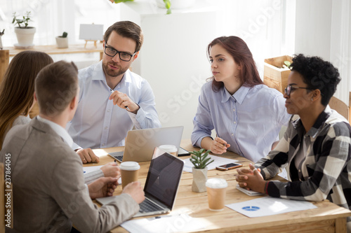 Stampa su Tela  Millennial businessman in glasses head casual office meeting talking to colleagu