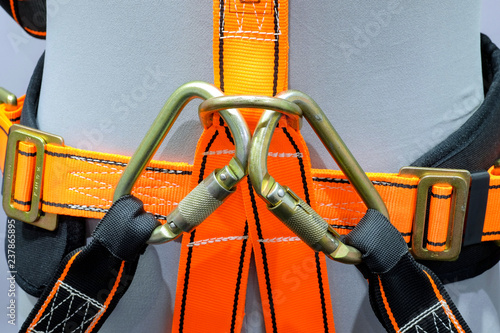 Fotografía  Close-up carabiners locked on safety belt on human model, a safety tools equipme
