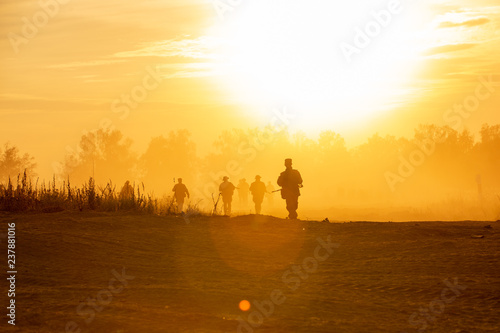 obraz dibond silhouette action soldiers walking hold weapons the background is smoke and sunset and white balance ship effect dark art style