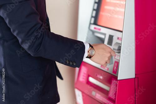 Obraz na plátne Businessman withdraw for cash at the ATM machine