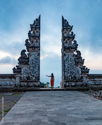 Girl is standing in the gate of Pura Lempuyang temple on Bali island, Indonesia