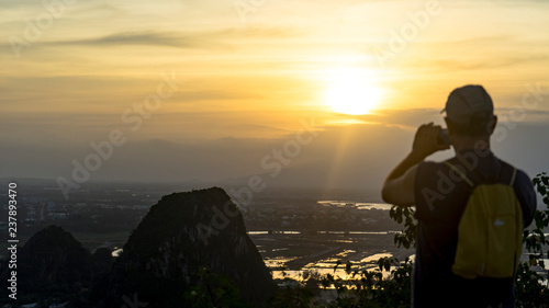 Fototapety, obrazy: Tourist staying on the top of mountain and taking a photos of Marble mountains and beautiful Da Nang city view with jungle and sea in sunset,travelling concept