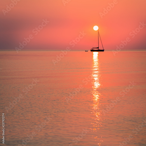 Fotografía  Sun resting on a sailing boat mast in living coral color sunrise, color of the year 2019