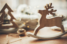 Rustic Reindeer Christmas Toy On Wooden Table On Background Of Lights, Wooden Tree, Twine, Gift In Linen With Green Branch, Pine Cones. Merry Christmas. Space For Text. Simple Eco Presents.