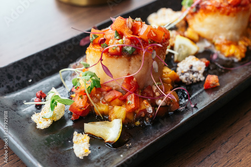 Spoed Fotobehang Klaar gerecht Grilled scallops with salsa lemon sweet and sour sauce.