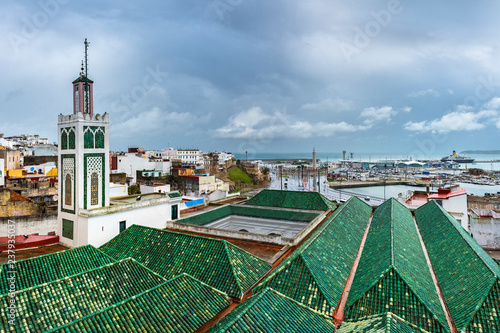 TANGIER / MOROCCO - NOVEMBER 2018: tiled roofs of buildings one of the many mosques of the medina of Tangier with a minaret and the kasbah / medina old quarter behind during the rain.