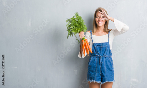 Obraz na płótnie Beautiful young woman over grunge grey wall holding fresh carrots with happy fac