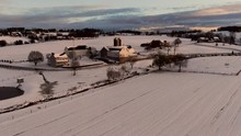 Wonderful Aerial Shot Overlooking Immense Snow Covered Farmland During Sunset