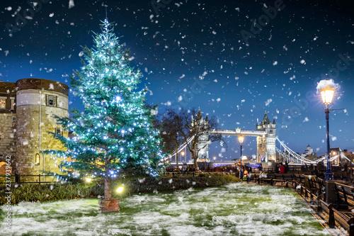 Winter in London Konzept: Weihnachtsbaum vor der Tower Bridge mit Schneefall bei Nacht