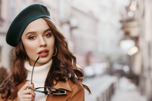 Outdoor Close Up Portrait Of Young Beautiful Woman With Long Hair Wearing Stylish Autumn Clothes, Green Beret, Holding Sunglasses, Model Posing In Street Of European City. Copy, Empty Space For Text