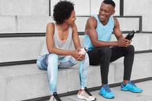 Motivated Cheerful Dark Skinned Woman And Man Sit At Stairs, Look Positively At Each Other, Hold Bottles With Water, Wear Sportclothes And Sneakers, Have Discussion About Sport Competitions.