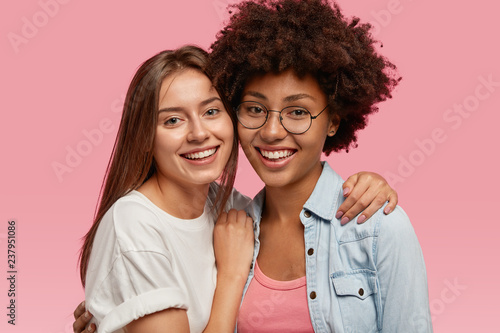 Foto  Portrait of friendly multiethnic women smile broadly, cuddle and enjoy togetherness, pose for family portrait, wear casual clothes, isolated over pink background