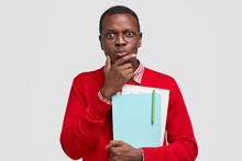 Photo Of Perplexed Indignant Black Man Holds Chin, Carries Folders And Papers, Stares At Camera With Stupefied Expressions, Being Busy With Learning And Studying, Isolated Over White Studio Wall