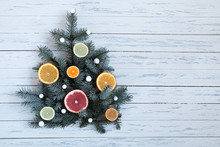 Christmas Tree With White Balls (snowflakes) And Oranges Tangerines, Grapefruits On A White Table