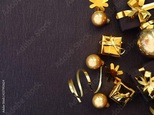 Fototapeta Merry Christmas and Happy New Year. Flat lay photo with black gift boxes, golden baubles on black background. Xmas greeting card, banner. Copy space for the text obraz na płótnie