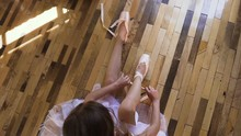 Top View. Ballerina Change Their Shoes Into Special Ballet Shoes, White Pointe Shoes, Lace With Ballet Ribbons. Young Ballerina In White Tutu Is Sitting On The Wooden Floor And Tied Ballet Shoes In