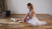 Ballerina Change Their Shoes Into Special Ballet Shoes, White Pointe Shoes, Lace With Ballet Ribbons. Young Ballerina In White Tutu Is Sitting On The Wooden Floor And Tied Ballet Shoes In The Ballet